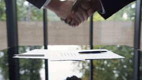 Nahaufnahme Zwei überzeugte Geschäftsleute, Afroamerikaner und Kaukasier, die Hände während einer Sitzung und eines Unterzeichnen stock footage