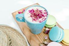 Nahaufnahmeansicht über Strohhut und blaue Schale Aromacappuccino mit französischen geschmackvollen macarons Lizenzfreie Stockbilder