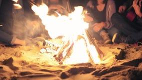 Nahaufnahmeansicht des Feuers spät nachts Junge Leute, die durch das Feuer am Abend, Gitarre spielend sitzen freundlich stock video footage