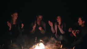 Nahaufnahmeansicht des Feuers spät nachts Junge Leute, die durch das Feuer am Abend, Gitarre spielend sitzen freundlich stock footage
