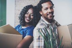 Nahaufnahmeansicht des jungen Schwarzafrikanermannes und seiner beweglichen Kästen der Freundin in neues Haus zusammen und ein sc Lizenzfreie Stockbilder