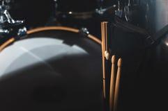Nahaufnahmeansicht eines der Trommel Satzes und Trommelstöcke in einem dunklen Studio Schwarze Trommelkörper mit Chromordnung Das lizenzfreie stockfotos