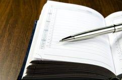 Nahaufnahmeansicht eines Metallstiftes, der auf dem Tagebuch mit einem Zeitplan liegt Stockbilder