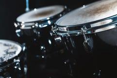 Nahaufnahmeansicht eines Trommelsatzes in einem dunklen Studio Schwarze Trommelkörper mit Chromordnung Das Konzept von Liveauftri stockbild