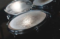 Nahaufnahmeansicht eines Trommelsatzes in einem dunklen Studio Schwarze Trommelkörper mit Chromordnung Das Konzept von Liveauftri stockfotografie