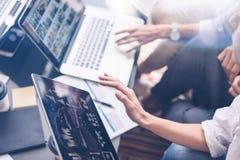 Nahaufnahmeansicht von den jungen Mitarbeitern, die an Laptop-Computer im Büro arbeiten Frau, die Tablettenhand hält und auf Note Lizenzfreies Stockfoto