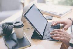Nahaufnahmeansicht von den männlichen Händen, die auf elektronischer Tablettentastaturdockstation schreiben Blogger, der im Büro  Lizenzfreie Stockbilder