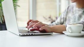 Nahaufnahmeansicht von Frau ` s übergibt das Arbeiten an Laptop-Computer Frau sitzt nahe dem Fenster im Café und im Schreiben Wei stock video footage