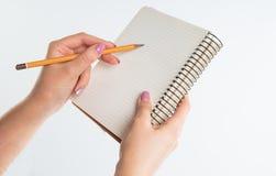 Nahaufnahmeansicht von Händen mit Sketchbook und Bleistift auf weißem Hintergrund Stockfotos