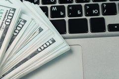 Nahaufnahmeansicht von hundert Dollarbanknoten, die auf der Laptoptastatur liegen stockfotografie