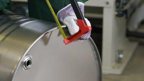 Nahaufnahmearbeitskraft in den Handschuhen schneidet mit glänzender Behälterseite der Metallsäge stock footage