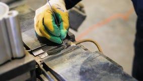Nahaufnahmearbeitskraft lötet Metallteil für zukünftige Batterien stock video footage