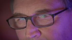 Nahaufnahmeaugenporträt des älteren Geschäftsmannes in den Gläsern die Texte lesend, die aufmerksam und konzentriert sind stock video footage