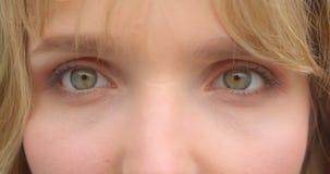 Nahaufnahmeaugenschuß des blonden Studenten mit grünen Augen aufpassend in die Kamera, die ernst und konzentriert ist stock video footage