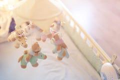 Nahaufnahmebabykrippe mit musikalischem Tiermobile am Kindertagesstättenraum Hanged sich entwickelndes Spielzeug mit flaumigen Ti stockfoto