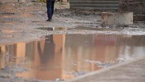 Nahaufnahmebeine der Person läuft am Wohnyard defekte schmutzige Straße mit enormer Pfütze durch, in der Mann reflektiert wird stock video footage
