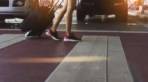 Nahaufnahmebeine des gehenden Schrittes der Frau auf Straße am Flughafen stockfoto