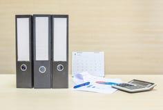 NahaufnahmeBelegdatei und Arbeitspapier und -taschenrechner im Konzept der harten Arbeit auf unscharfem hölzernem Schreibtisch un Stockbilder