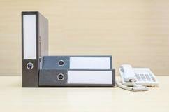 NahaufnahmeBelegdatei und weißes Telefon, Bürotelefon auf unscharfem hölzernem Schreibtisch und Wand maserten Hintergrund im Konf Stockfotografie