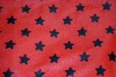 Nahaufnahmebeschaffenheit eines roten Gewebes mit schwarzen Sternen Stockfoto
