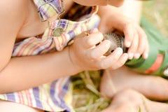 Nahaufnahmebild auf den Kinderhänden, die Bohrgerät und Stückchen halten Lizenzfreie Stockbilder