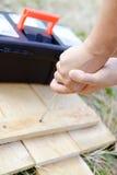 Nahaufnahmebild auf Händen mit Schraubenzieher und Stockbild