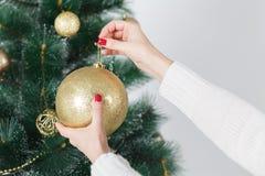 Nahaufnahmebild der Frau in der Strickjacke Weihnachtsbaum mit Flitter verzierend Lizenzfreies Stockbild
