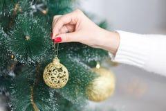 Nahaufnahmebild der Frau in der Strickjacke Weihnachtsbaum mit Flitter verzierend Lizenzfreie Stockfotografie