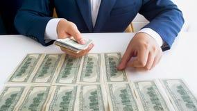Nahaufnahmebild des reichen Geschäftsmannes sitzend im Büro und Geld in den langen Reihen auf Schreibtisch legend stockfoto