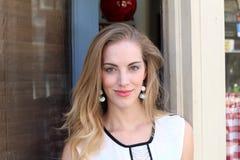 Nahaufnahmebild des schönen blonden Mädchens, das einen Shop herausnimmt Lizenzfreie Stockfotos