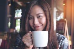 Nahaufnahmebild einer schönen Asiatin, die heißen Kaffee mit dem Fühlen gut hält und trinkt Lizenzfreies Stockfoto