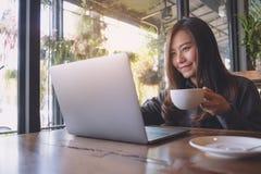 Nahaufnahmebild einer schönen asiatischen Geschäftsfrau, die an Laptoptastatur beim Trinken des Kaffees arbeitet und schreibt Stockbild