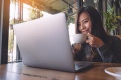 Nahaufnahmebild einer schönen asiatischen Geschäftsfrau, die an Laptoptastatur beim Trinken des Kaffees arbeitet und schreibt Lizenzfreies Stockfoto