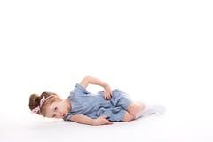 Nahaufnahmebild eines recht kleinen Mädchens, das auf dem Boden sitzt Lizenzfreie Stockfotografie