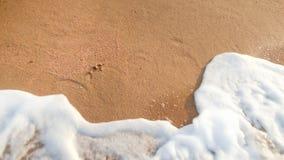 Nahaufnahmebild von den Meereswogen, die über perfektem goldenem Sand auf Inselstrand rollen lizenzfreies stockfoto