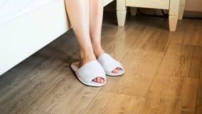 Nahaufnahmebild von den weiblichen Füßen, die weiße Hotelpantoffel am Bett tragen lizenzfreie stockbilder