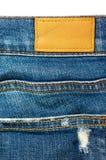 Nahaufnahmeblue jeans mit ledernem Aufkleber Stockbild