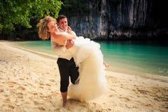 Nahaufnahmebräutigam trägt bewaffnet herein blonde Braut in flaumigem auf Strand Lizenzfreie Stockfotos