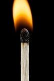 Nahaufnahmebrennendes zündholz mit Flamme auf schwarzem Hintergrund Lizenzfreie Stockfotografie