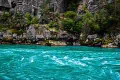 Nahaufnahmedetailbild von einem Fluss mit blauem Wasser des Türkises und von felsigen Ufer bedeckt mit Bäumen und Moos in Norwege lizenzfreies stockfoto