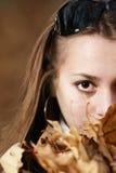 Nahaufnahmefallportrait des jungen Mädchens mit Laub Stockfotografie