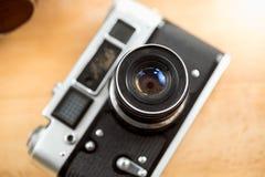 Nahaufnahmefoto der alten Filmkamera, die auf hölzernem Schreibtisch liegt stockfoto