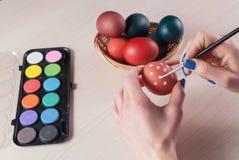 Nahaufnahmefoto der Frau Ei halten und es mit Bürste malend lizenzfreie stockfotografie