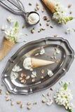 Nahaufnahmefoto der frischen Eiscreme auf Metallbehälter mit weißen Blumen und Nüssen Lizenzfreies Stockbild