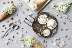 Nahaufnahmefoto der frischen Eiscreme auf Metallbehälter mit weißen Blumen und Nüssen Beschneidungspfad eingeschlossen Lizenzfreies Stockbild