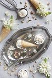 Nahaufnahmefoto der frischen Eiscreme auf Metallbehälter mit weißen Blumen und Nüssen Beschneidungspfad eingeschlossen Stockbilder