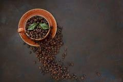 Nahaufnahmefoto der heißen Aromaschale mit Kaffee und Kaffeebohnen auf schwarzem Tabellenhintergrund Lizenzfreies Stockbild