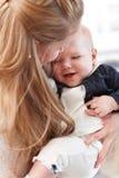 Nahaufnahmefoto der Mutter Baby umarmend Lizenzfreie Stockbilder