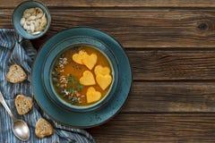 Nahaufnahmefoto der Platte mit frischer selbst gemachter Kürbiscremesuppe mit Samen und Herz formen Toast auf hölzernem Hintergru Stockbilder