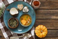 Nahaufnahmefoto der Platte mit frischer selbst gemachter Kürbiscremesuppe mit Samen und Herz formen Toast auf hölzernem Hintergru Stockfoto
